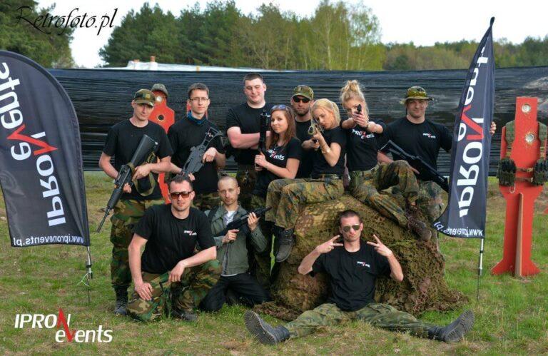 grupka osób ubrana w czarne koszulki i spodnie moro, uśmiechająca się do zdjęcia