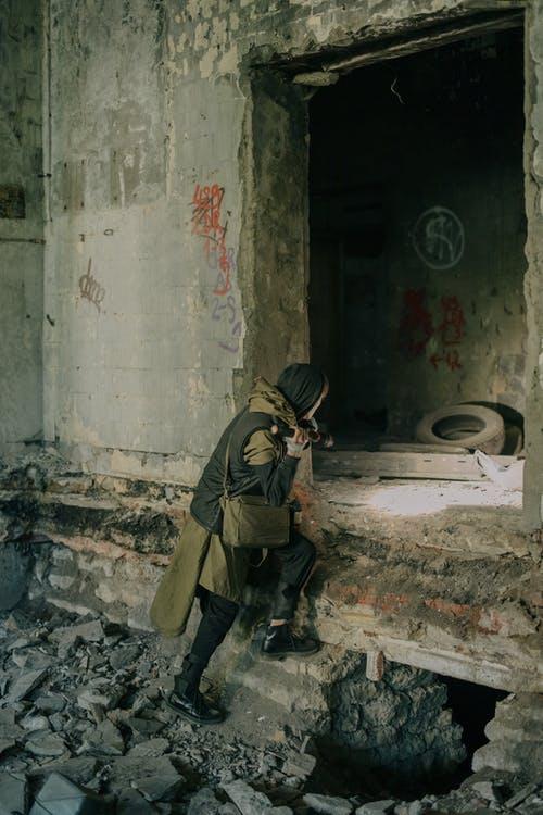 człowiek wchodzący do opuszczonego budynku
