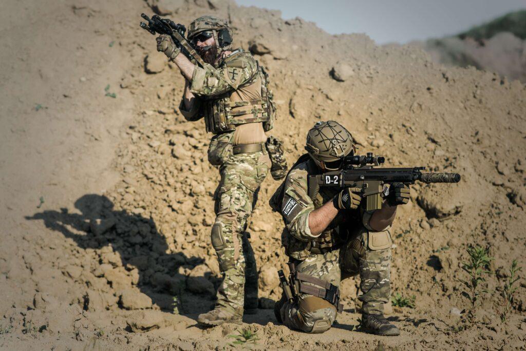 dwóch wojskowych celujących do czegoś z broni
