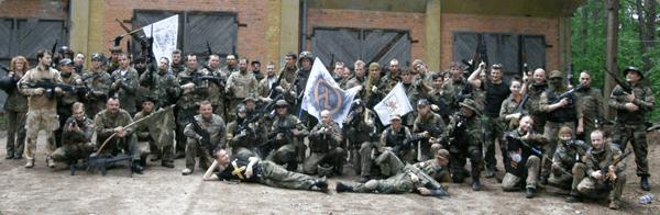 Grupa pozująca do zdjęcia ubrana w strój moro trzymająca flagi