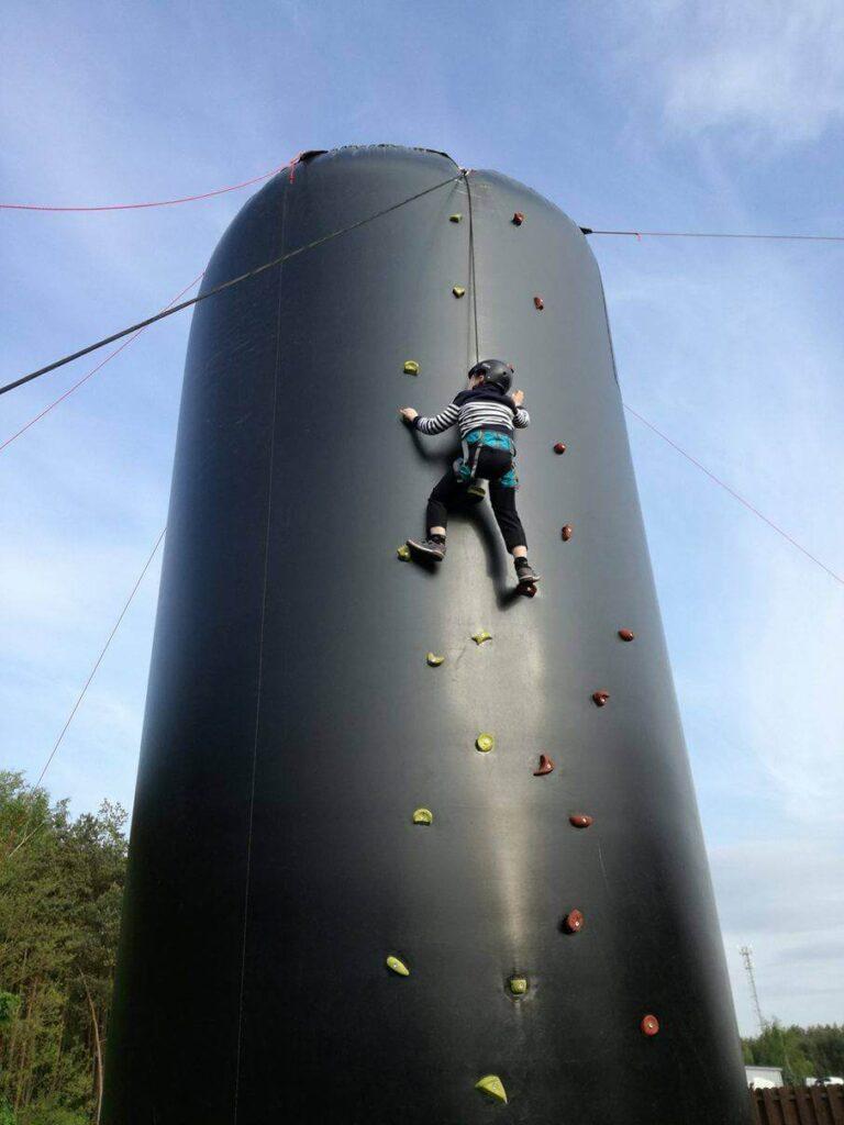 dziecko wspinające się po dmuchanej ściance wspinaczkowej