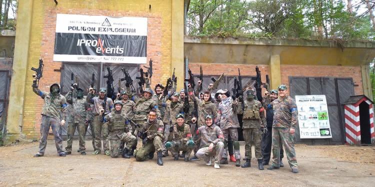 Grupa ludzi trzymająca broń ASG w górze